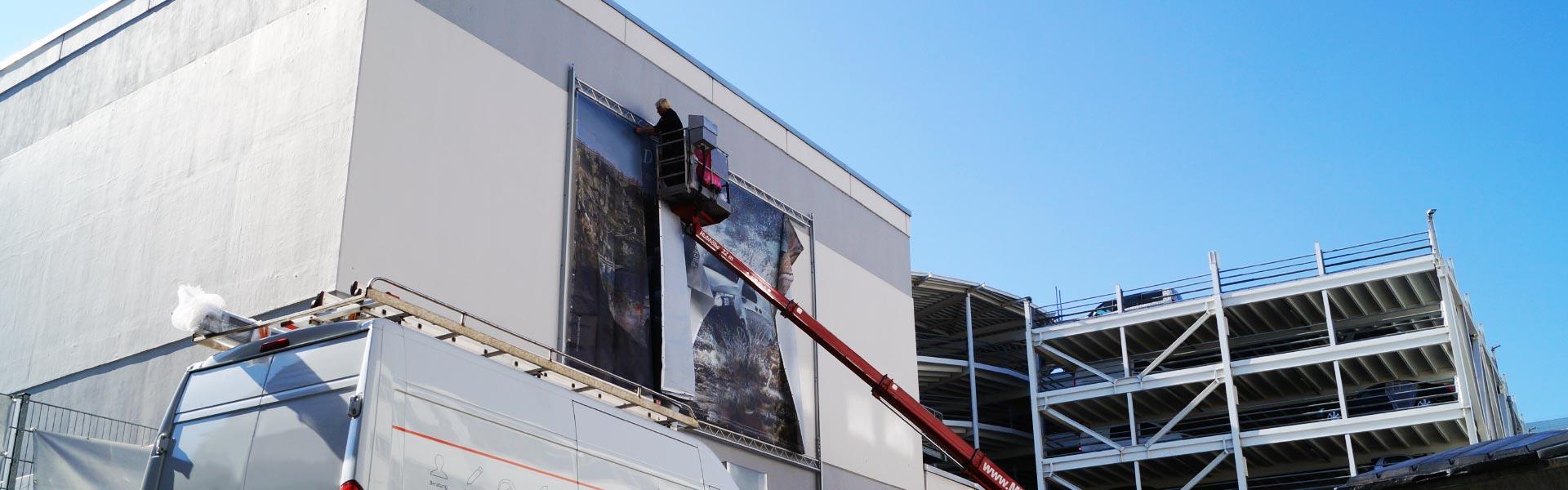 Befestigung eines Werbebanners an einer Fassade zur Darstellung von Fassadenwerbung