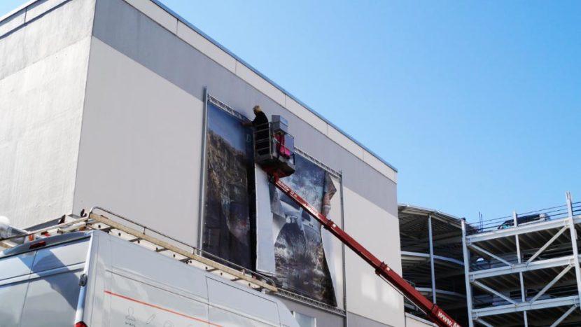 Befestigung eines Werbebanners an einer Fassade zur Darstellung von Fassadenwerbung, Titelbild