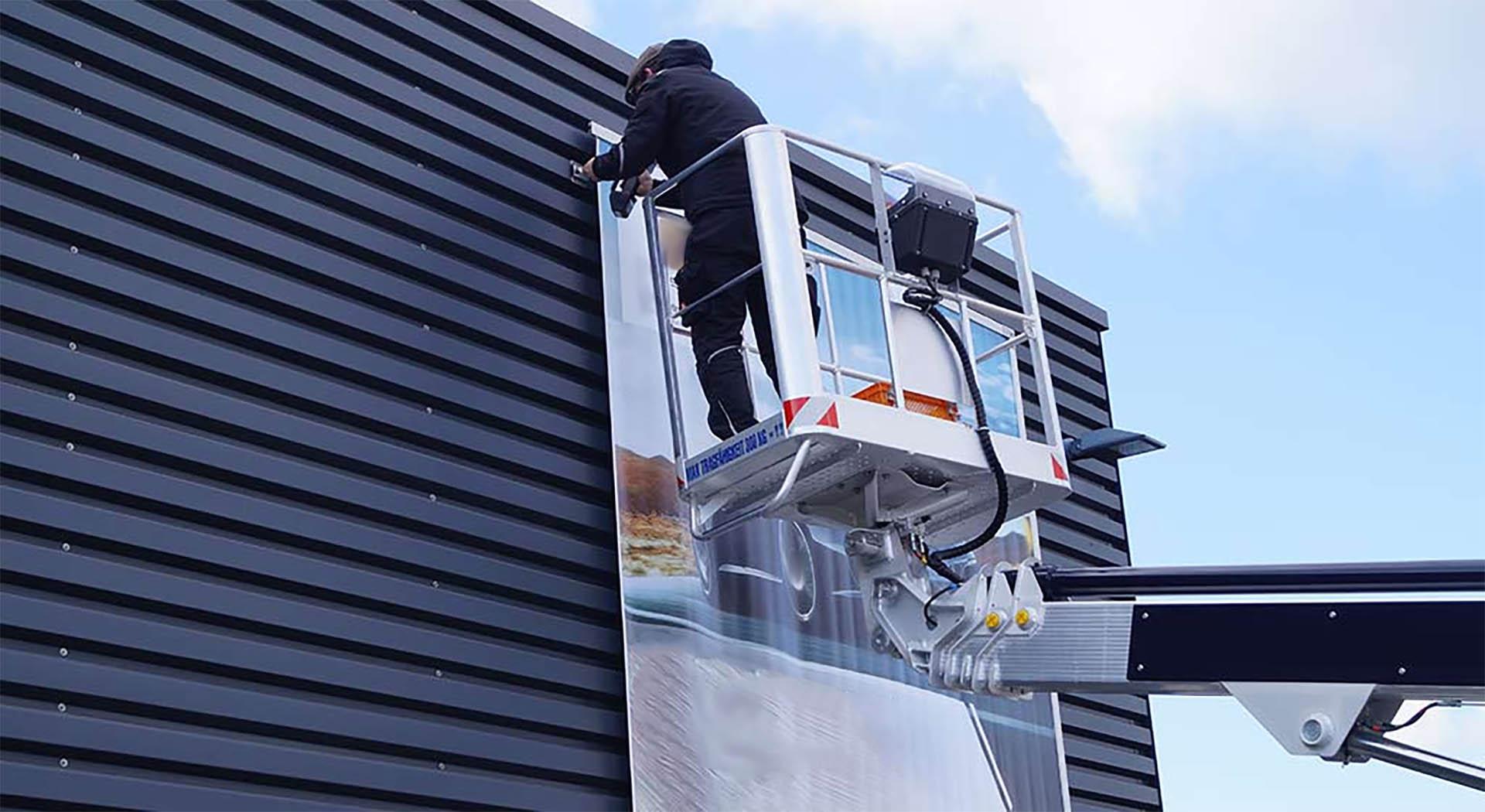 Anbringen von Außenwerbung an einer Fassade mit Hubwagen