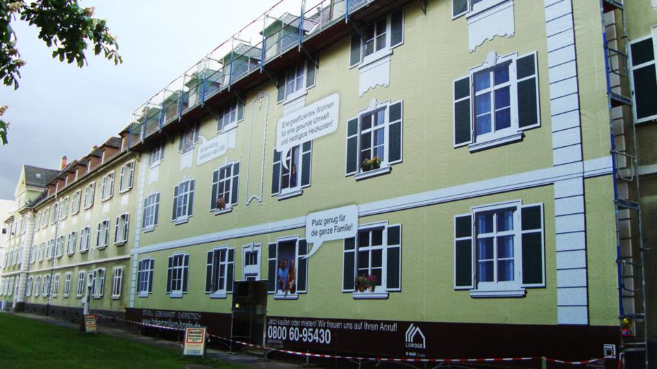 Fassaden- bzw. Gerüstverkleidung: Baugerüste können mit Bannermaterial zu Werbezwecken verkleidet werden um großflächige Werbung zu zeigen. Ansicht eines Gebäudes mit Gerüstvkleidung aus seitlicher Sicht.