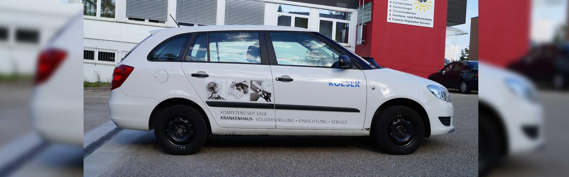 Ein beschrifteter Kleintransporter mit einer Teilbeklebung des Fahrzeuges.