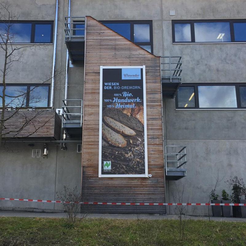 Fassadenwerbung mit dem Werbelifter+. Befestigen Sie großformatige Werbebanner mit dem komfortablen Liftsystem, für die Firma Wiesender.