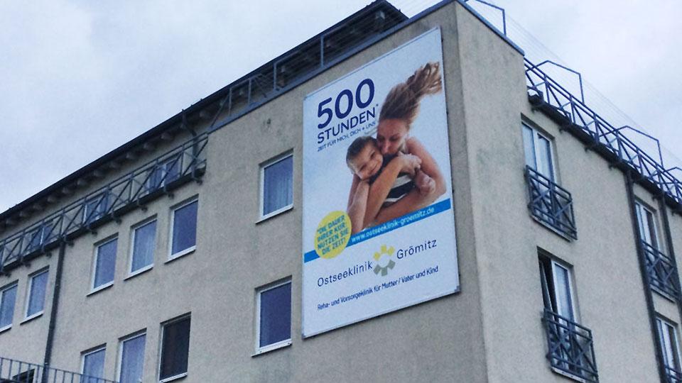 Nahaufnahme der Fassade der Klinik mit der neuen Werbeanlage mit dem Kederrahmen+